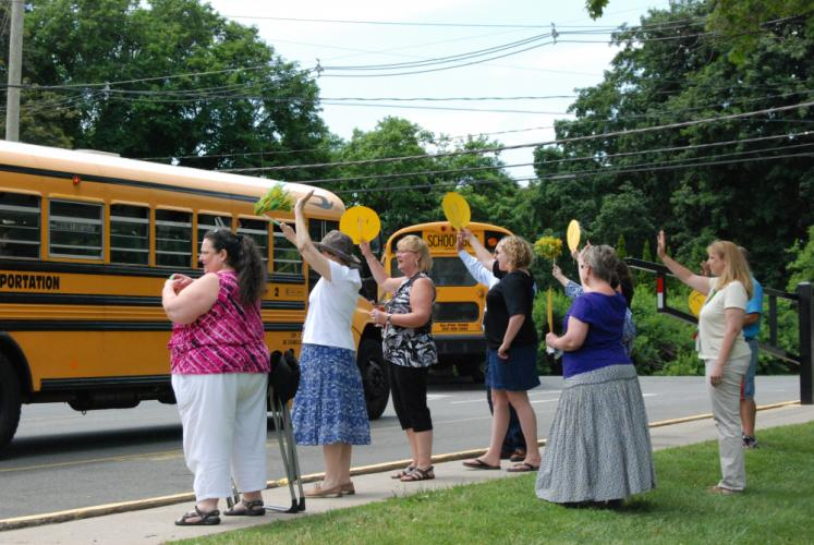 Teachers from Newtown Middle School hold up paper cut-outs of smiley faces and wave, as they say goodbye to students aboard the buses.  (Bee Photo, Preszler)