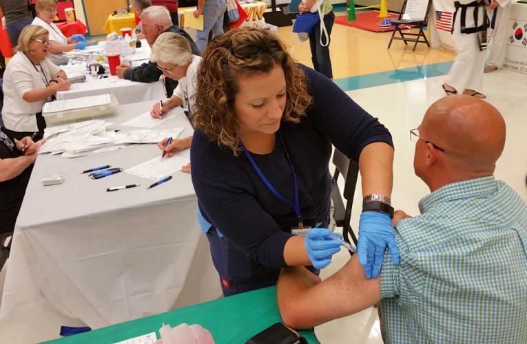 Ryland Edwards of Sandy Hook gets his annual flu shot from Bethel VNA Registered Nurse Janette Basham.