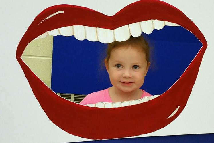 Ainsley Irwin puts on a smile in more ways than one at the Newtown family Dentistry booth.