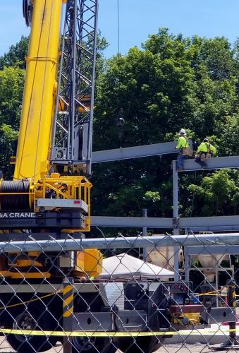 Steel workers manipulate a crossbeam into place Monday, July 9, as the 'bones' of the new community and senior center building take shape. (Bee Photo, Voket)