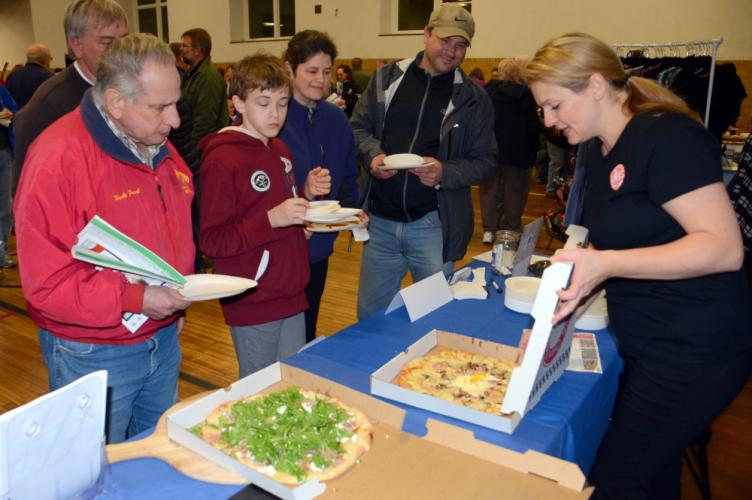 """PIY (Pizza It Yourself) owner Grace Winstanley, right, opens up a couple of freshly delivered pies as 2017 Destination Newtown attendees queue up for a slice. The local """"internet pizza company"""" specializes in helping customers create and bake their…"""