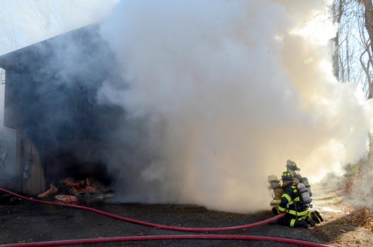 Smoke engulfs a garage at 2A Fir Tree Lane, November 26, as firefighters from Sandy Hook Volunteer Fire & Rescue and Newtown Hook & Ladder train hoses on the burning structure.  (Bee Photo, Voket)