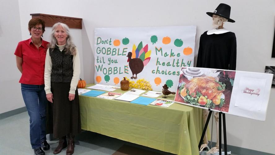 Newtown Health District Food Service Inspector Suzette LeBlanc, left, and administrative assistant Maureen Schaedler stand beside a seasonal information display in the Municipal Center that Ms Schaedler helped create to provide a one-stop location…