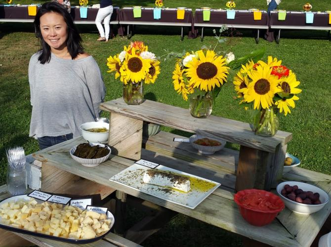 Holbrook Farm in Bethel is managed by farmer Jessica Wong, pictured beside the appetizer table at her August 27 farm dinner. She is hosting the third of this season's three dinners.  (Bee Photos, Voket)