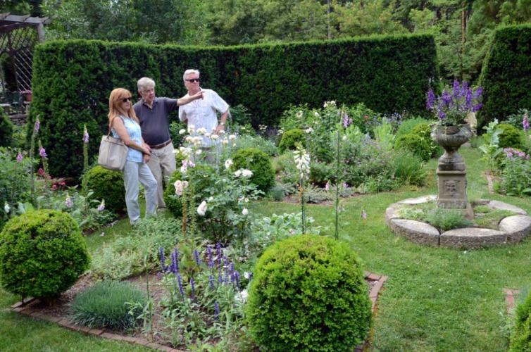 Lincoln Sander points out a feature in his English Garden to Home & Garden Tour visitors Ken and Barbara Donahue.