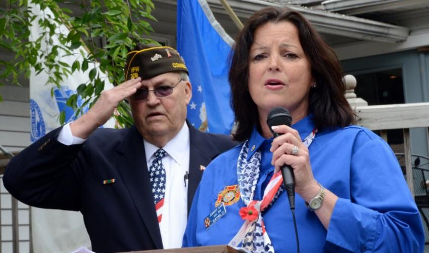 """Newtown VFW Post Quartermaster Michael Mich salutes as Post Auxiliary member Jennifer Clark sings """"God Bless America,"""" closing Memorial Day ceremonies May 28."""