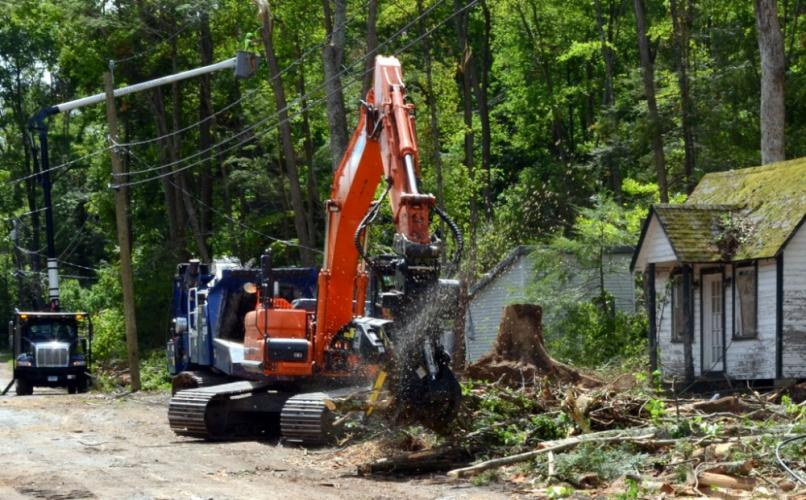 Flying sawdust can be seen as the combination claw and cutter continues its work detangling and clearing fallen trees from the May 15 microburst in the Cedarhurst community in Sandy Hook.  (Bee Photo, Voket)
