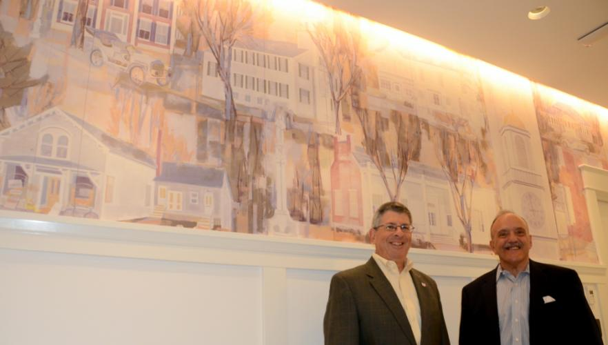 A detailed mural highlighting a number of Newtown landmarks serves as a backdrop for Newtown Savings Bank Executive Vice President Ken Weinstein, left, who will be assuming the role of president and CEO following the December 31 retirement of…