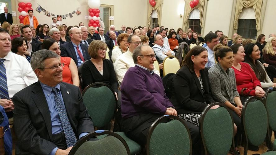 Retired Newtown Savings Bank President and CEO John Trentacosta, second from left, laughs from his front row seat during a farewell retirement testimonial thrown by his employees, many of whom joined the respected bank executive at the Edmond Town…
