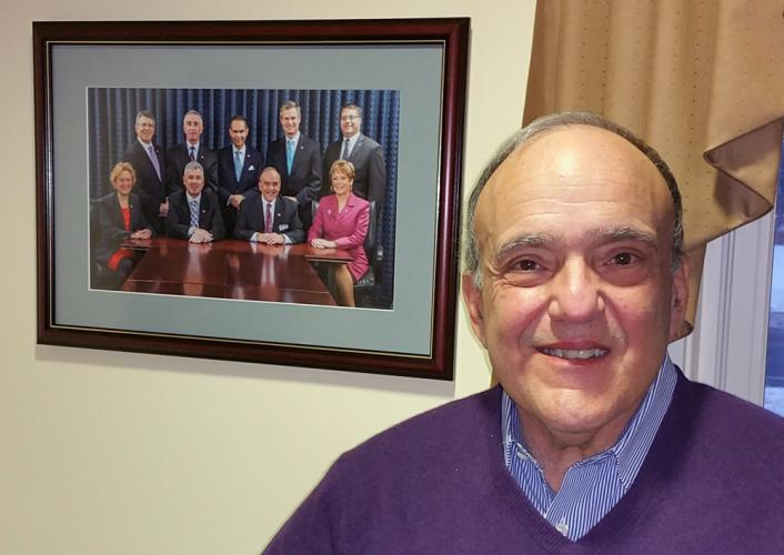 Retired Newtown Savings Bank President and CEO John Trentacosta stands before a photo of the bank's executive team, most of whom he hired or recruited to the local financial institution. Mr Trentacosta has been succeeded by Kenneth L. Weinstein, but…