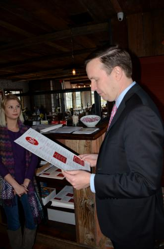 Hostess Samantha Phillips looks on as Senator Chris Murphy peruses the menu at Market Place Kitchen & Bar during a brief tour of the Village at Lexington Gardens, March 28.