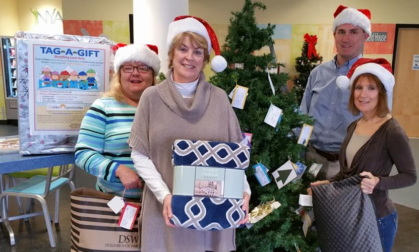 Several local volunteers, from left, Laura Branchini, Karen Harris, and Lynette Daria have continued supporting the Newtown Tag A Gift program. They gathered with NYA Sports & Fitness Director Nick Hoffman this week to install a collection box in…