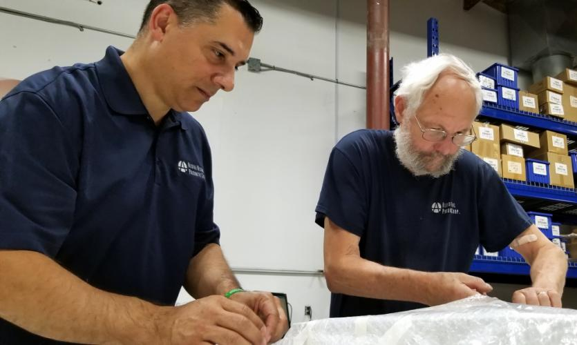 Aldine Metal Products Corp CEO Rod Blessey, left, assists fellow Newtown resident and shop employee Randy Botk packaging a recently machined metal cabinet part for one of the New Milford company's many national and international clients.