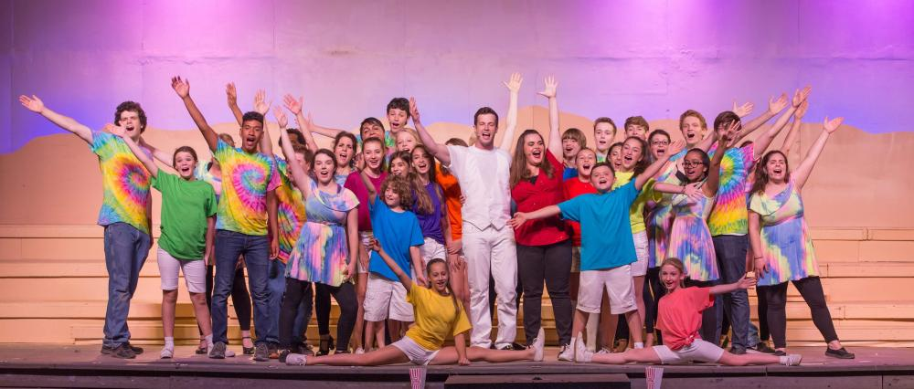 Joseph (Connor Spain, center) is encouraged to follow his dreams by the Narrator (Katie Cummings, center in red) and the full company in <i>Joseph and the Amazing Technicolor Dreamcoat,</i> in production for two more weekends at Danbury's Musicals…
