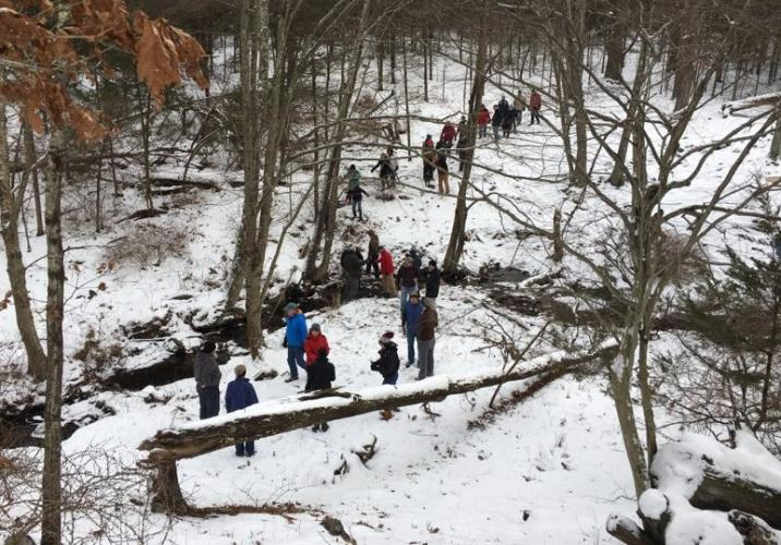 Participants in a hike at Cherry Grove farm on December 16 are seen crossing a stream in a small valley before scrambling up a rise. The hike was sponsored by Newtown Forest Association, which is hoping to raise the necessary funds to acquire and…