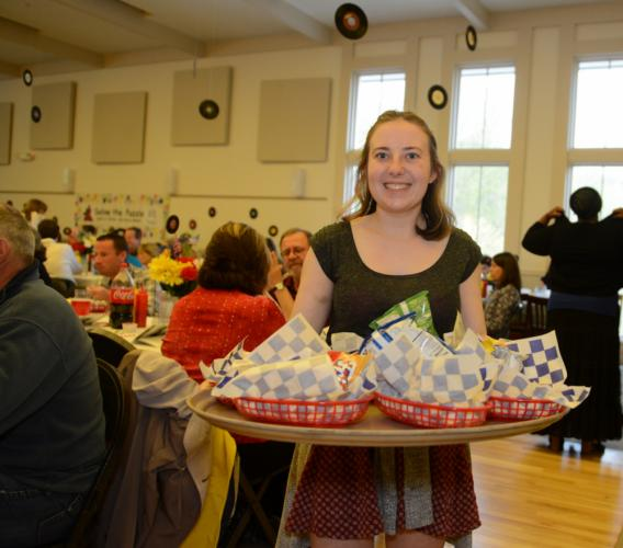 "Julia Faxon serves snacks during the dinner hour at the Families United In Newtown event on May 14. The evening, ""A Celebration of Rock & Roll Music,"" featured a car-hop style dinner and music from the 1950s and 60s.  (Bee Photo, Bobowick)"