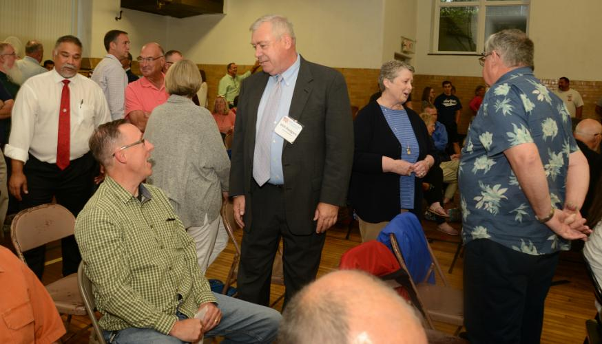 Republican Selectman Will Rodgers, center, chatting with Police Commissioner Brian Budd, and accompanied by his wife and former Newtown Probate Judge Moira, won the party's endorsement for First Selectman during a crowded July 24 caucus at Edmond…
