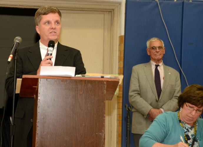 Republican Board of Education member Andy Clure, at podium, speaks to party members during a July 24 GOP caucus at Edmond Town Hall as caucus moderator Robert Hall and Republican Registrar Carey Schierloh look on.   (Bee Photo, Bobowick)