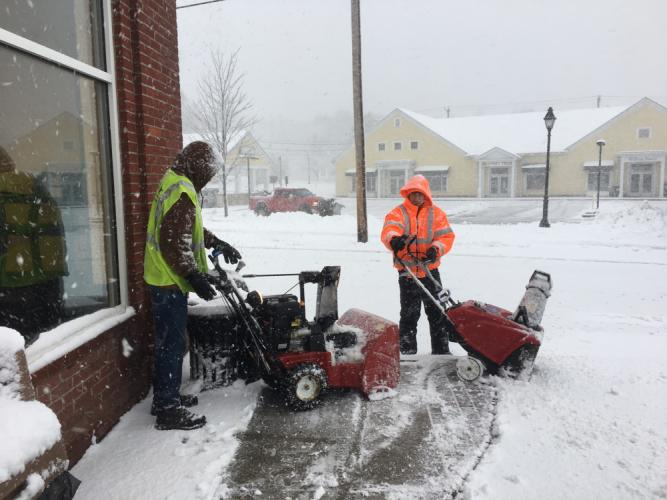 Construction and landscape crews stayed busy late Wednesday afternoon clearing snow from the sidewalks outside businesses at Queen Street Shopping Center.  (Bee Photo, Bobowick)