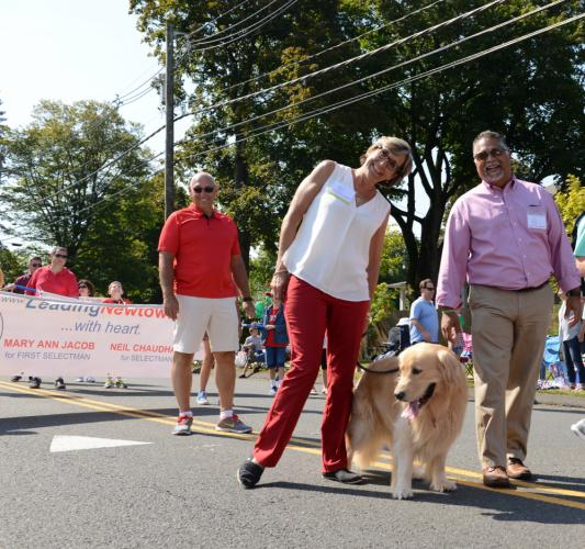 First Selectman candidate Mary Ann Jacob and selectman candidate Neil Chaudhary walk with Ms Jacob's dog Calvin at the Labor Day Parade. (Bee Photo, Bobowick)