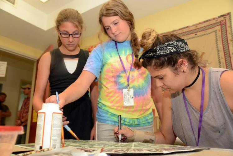 From left are Michaela Bonacci, Maria Goldstein, and Becky Romano, who were painting props on July 11, in one of the production offices temporarily houses at Newtown Congregational Church, to be used in the NewArts summer production of 'Newsies.'