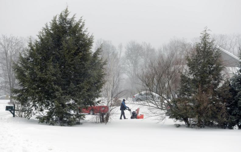 As wind continued to whip sleet and snow Tuesday, many residents sensed the end of the storm by midafternoon and began the cleanup. One Loveland Drive resident was among the first in the neighborhood to start up his snowblower.  (Bee Photo, Bobowick)