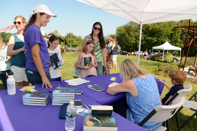 Jolene and Jack Brackett and mom, Carrie, of Newtown, step toward children's author Katherine Applegate for a book signing.