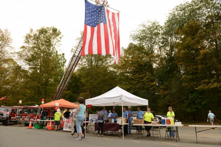 Sandy Hook Organization for Prosperity members and FAITH Food Pantry representatives find shade beneath awnings in the rear parking lot at 100 Church Hill Road. Behind their tables is a flag suspended by a Sandy Hook Volunteer Fire & Rescue truck. -…