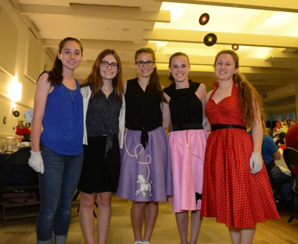 Among those serving the many dinner guests Saturday night and dressed in polka dots and poodle skirts were, from left, Sarah Mawdsley, Laura Humbly, Cassidy Keller, Kelsey Milner, and Rachel Crosby.  (Bee Photo, Bobowick)