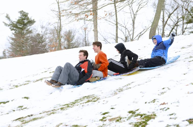 Kyle Trahan is first in line as he and friends, Matthew Weisgerber, Aidan Stout, and Jenna Reilly pass Tuesday afternoon on their sleds at Treadwell Park.  (Bee Photo, Bobowick)