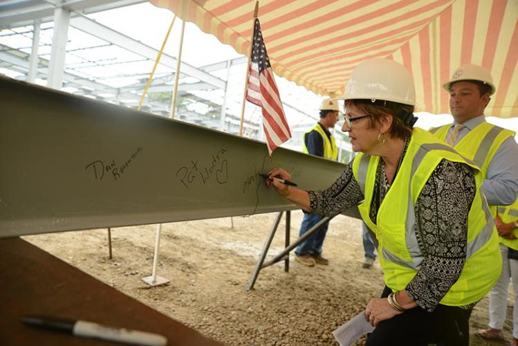 Setting her name next to past First Selectman Pat Llodra and current First Selectman Dan Rosenthal is Senior Center Director Marilyn Place. Behind her is Community Center Director Matthew Ariniello. She and others signed the final construction beam…