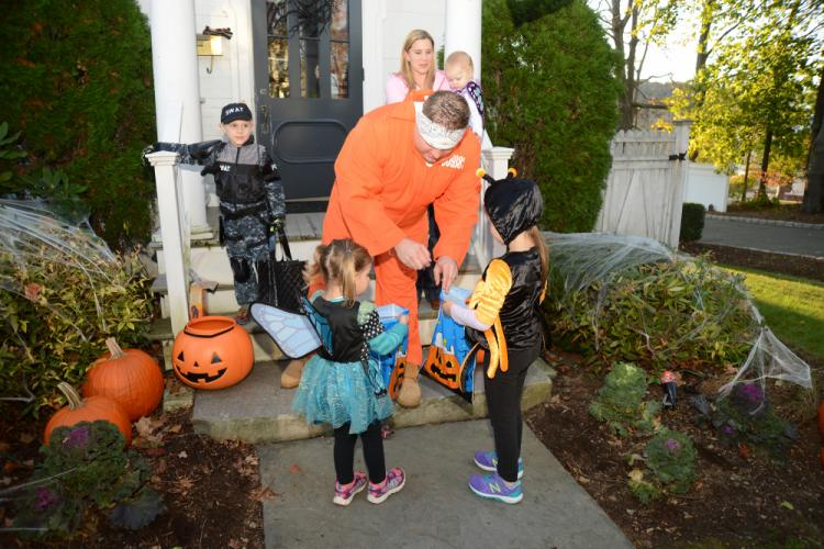 """Inmate"" Ben Champagne hands candy to guests Tuesday evening. He borrowed his sister Sarah Phillips's front stoop at 35 Main Street. Behind him are his wife Andrea holding daughter Ava, and son Noah, dressed in a SWAT outfit. --Bee Photo, Bobowick"