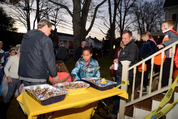 40 Main Street homeowner John Madzula, right, smiles as he watches the steady stream of trick-or-treaters help themselves to candy. --Bee Photo, Bobowick