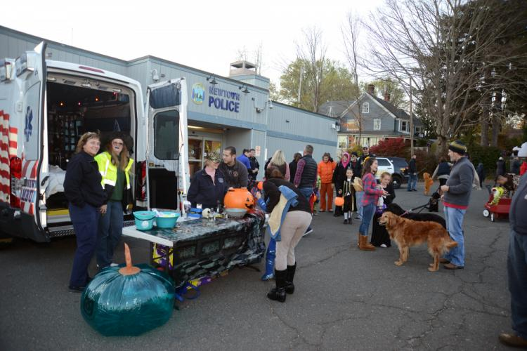 "For the first time this year, Newtown Volunteer Ambulance Corps members handed out treats safe for children with allergies, and other ""safe toys,"" to the hundreds of costumed guests passing through the Newtown Police Department parking lot, Tuesday…"