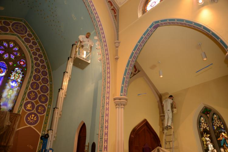 Men with Artech Church Interiors of Woodbury stand on ladders and motorized lifts to reach all areas they are repainting and repairing. -Bee Photos, Bobowick
