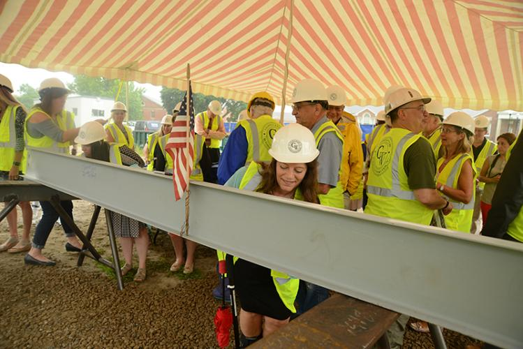 With an overhang shielding her from Wednesday morning rain, Town Clerk Debbie Aurelia Halstead was among several dozen people gathered to see the final Newtown community and senior center beam set in place. Ms Aurelia signs the ink in permanent…