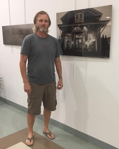 """Phil Keane stands with one of the photos currently on view in """"Images of Newtown's Past,"""" an exhibition of his photographs on metal on view at Newtown Municipal Center through the end of October. The public is invited to meet the artist and view the…"""