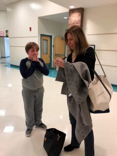 Author Lauren Tarshis signs a note for excited Reed Intermediate School student Jacob Petrini on December 8, during a visit to the school. (Pia Ledina photo)