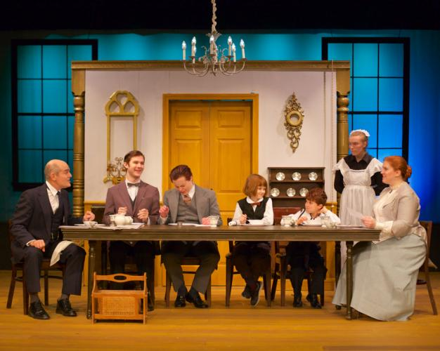 The Day family at dinner: Clarence Day, Sr (portrayed by Steve Manzino), Clarence Jr (Tim Vlangas), John (Alex Desjardin), Whitney (Maureen Previn) Harlan (Elias Osborne) and the matriarch Lavinia (Stacy-Lee Frome), with the maid Annie (Mary…