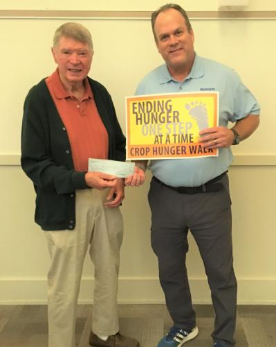 Gordon Williams, left, of Newtown Lions Club, recently presented a check on behalf of the local Lions to Reverend Matt Crebbin, right, chairman of the CROP Hunger Walk of Newtown/Sandy Hook, to help with this year's fundraiser. This year's CROP Walk…