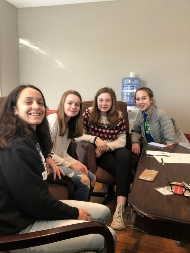 Newtown Middle School Project Challenge students, from left, Kirtana Kunzweiler, Ava Hanson, Emily Jackson, and Anna Ochs pose together for a photo. The students held a bake sale over the weekend of April 1 to raise money to build a well in Liberia.