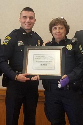 Newtown Police Officer Maryhelen McCarthy was presented The Chief Michael J. Fallon Memorial CIT Officer of the Year Award during the annual Crisis Intervention Teams symposium in Storrs. Standing with Ofc McCarthy is  Officer Michael Fallon of…