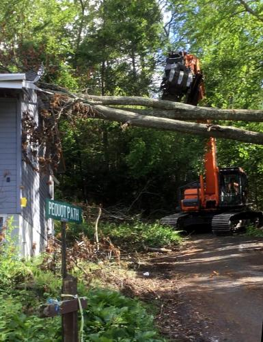 One of the specialty pieces of equipment brought in for the heavy storm cleanup this week is a combination claw crane and log cutter, pictured here removing a fallen tree from one of the residences in the Lakeview Terrace neighborhood.  (Courtesy …