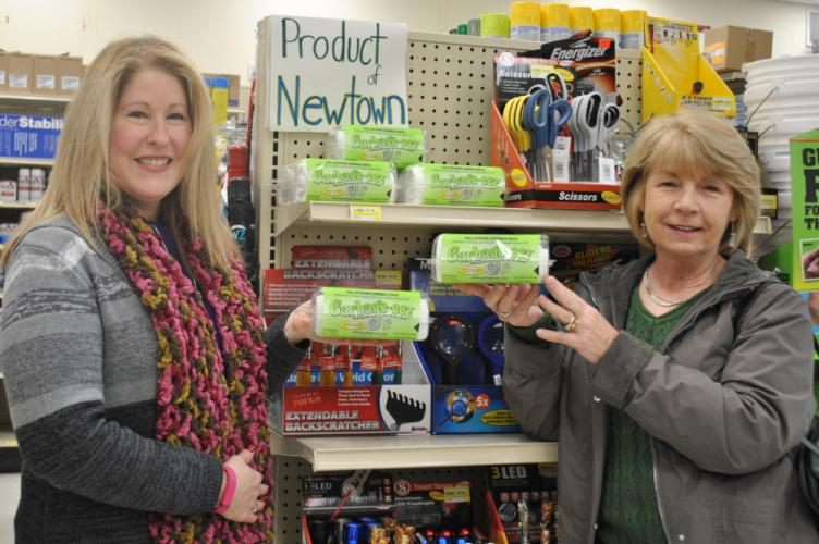 Stacey Lokey, left, and Carolyn Caplic, creators of Garbage-eez, stand next to a display of their product in Newtown Hardware. The local hardware store was the first to put Garbage-eez on the shelf and into the hands of consumers, late last summer.…