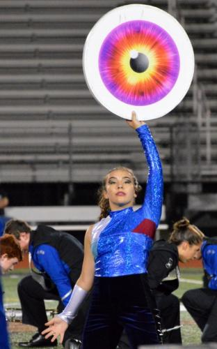 NHS Guard member Tess Trahan holds up a prop during the Marching Band & Guard's performance of the show Dystopia on October 7.  -Denise Romano photo