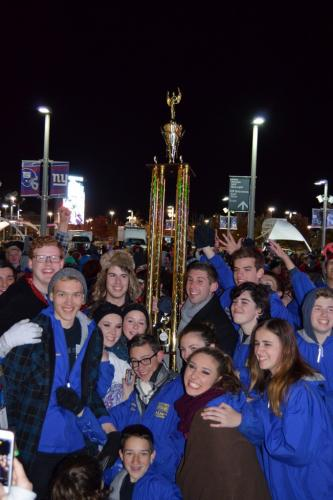 NHS Marching Band & Guard Visual Caption Head Ricky Grasso holds the trophy, while excited students surround him at Nationals. (Denise Romano photo)