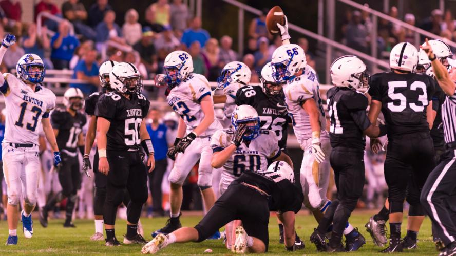 Nighthawk football players celebrate a fumble recovery against Xavier as Jack Street holds up the ball. (Mike Salaris photo)