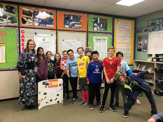 Reed Intermediate School sixth grade teacher Julie Shull, left, stands with some of her students on November 16, as they wear clothing inspired by International Education Week.