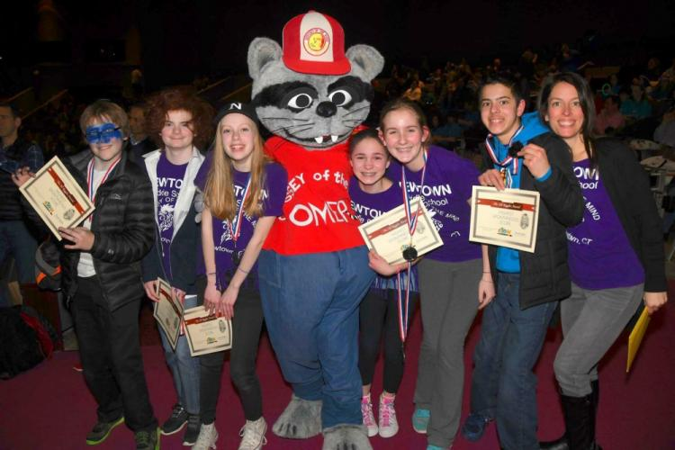 Standing with the Odyssey of the Mind Mascot at the state tournament on March 18 are coach Kristina Tartaglia, right, and her team members, from left, Joseph Tartaglia, Willem Doherty, Luke Sordi, Maddie Hintze, Mackenzie Hughes, and Lenie Urbina.