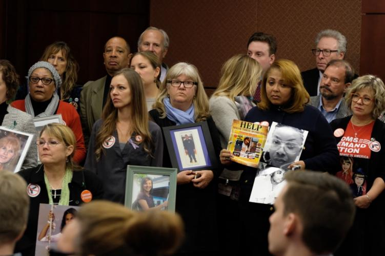 A group of gun violence survivors hold images of their lost loved ones during a December 6 press conference in Washington, DC. (Philip Keane photo)